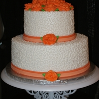 Orange Roses Wedding Cake  2 tier marble cake iced all in buttercream, then overpiped with cornelli lace, fondant ribbon, buttercream roses. This one was my first...