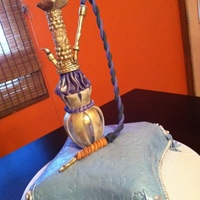 Hookah Cake Bottom part is made out of a small glass vase covered in fondant and pipe is a plastic dowel covered in fondant painted gold luster dust....