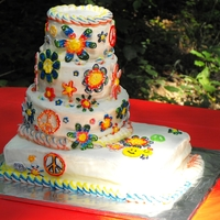 Tie-Dye Wedding Cake Four stacked tiers of red velvet cake with cream cheese buttercream and royal icing flowers and peace signs colored with icing gel/vodka...