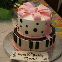 Piano Cake   Top tier is SMB with fondant polka dots. Bottom is ganache with fondant piano keys. Pink fondant bow on top.