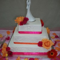 Janczi And Justins Cake 3 tier square cake iced in BC with fresh flowers. The wedding colors were orange and pink with burlap accents.