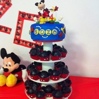 Mickey Mouse Cupcake Tower Mango flavored cupcakes and cake with mango buttercream filling. Cupcakes mickey ears are all made of fondant/gumpaste.