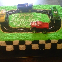 Race Track Cake sheet cake all buttercream track is made out of oreos i bought some trucks and placed them on the car..