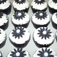Black & White Cupcakes boxed individually & used as favours for guests at a 5oth birthday meal.Pure white buttercream, black gerberas & a touch of edible...