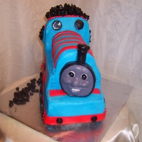 Tommy Cake is covered in blue butter cream icing. the detail work is red and black fondant.
