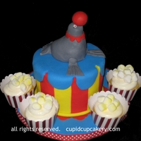 Circus Cake   Circus themed birthday cake with a little fondant seal. Cupcakes were made to match the circus theme.