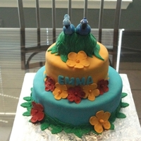 Rio Tiered cake in rolled fondant with gumpaste flowers and plastic figurines.