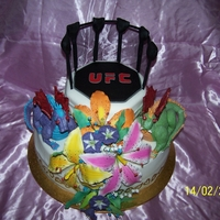 Ufc/dragon/tiger Lilly Cake bride wanted UFC and rough looking dragons with tiger lillys and this is what i came up with choc mud cake with ganache filling and fondant...