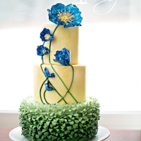 Blue Poppy Cake Ombre green grass ruffles covered the bottom tier. Two yellow tiers brushed with gold dust and highlighted with bright blue poppies. I...