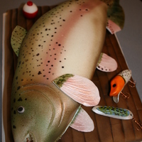 If You Can't Catch One...make One!  For our friends birthday who loves to fish. Cutting board is one layer of chocolate with brushed fondant. Fish was carved, covered in...