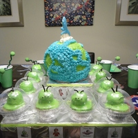 Earth Cake With Alien Cupcakes A planet earth cake with a chocolate rocket blasting off. Completed with aliens in their space ships. All for an awesome oiter space...