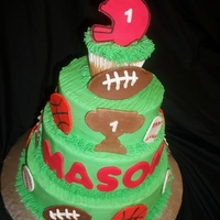 "Sports Themed First Birthday 6""/8""/10"" round vanilla cakes with buttercream icing and fondant accents. Topped with a jumbo cupcake that was removed as..."