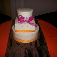 "Orange And Pink Wedding Cake  6"" round/8"" square/12"" round cake. Each tier was 1/2 vanilla, 1/2 red velvet. Buttercream icing and ribbon and broach..."
