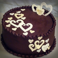 Swirling Hearts Chocolate cake with caramel filling and ganache icing. Fondant hearts dusted with gold and pearl luster dust. TFL!