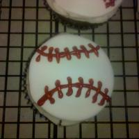 "Baseball Cupcakes Cupcakes topped with butter cream and Fondant and royal icing ""stitching"""