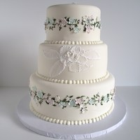 Delicate Flowers A wedding cake I made for my cousin. I painted the green vines on the cake and then added gumpaste flowers. The middle tier was my atempt...