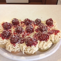 Spaghetti Cupcakes Vanilla cake with classic vanilla frosting, raspberry jam and Ferrero chocolates as meatballs. White chocolate shavings used as cheese