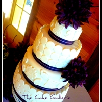 Linganore Winery Wedding Cake A 4 tiered fondant cake with purple ribbon and purple flowers with wine vinyard branches as decoration. lemon zest cake with vanilla butter...