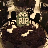 Graveyard Cupcakes   These were made for my daughters class Halloween party. Bones and tombstones made with royal icing and fondant, dirt is crushed cookies