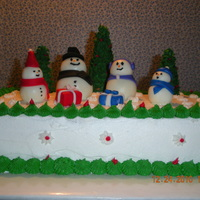 Christmas Cake   Chocolate cake, buttercream icing, fondant snowmen, trees are sugar cones with royal icing