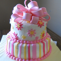 Pink And Yellow Stripes And Flowers With Bow  2-tier yellow cake, 6 inch and 8 inch, with buttercream frosting and border and MMF stripes, flowers, and bow. Made for a birthday on 3/19/...