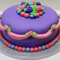 Pink And Purple Princess Cake  8 inch banana cake with chocolate buttercream covered in marshmallow fondant. All decorations also done in marshmallow fondant. For a 2-...