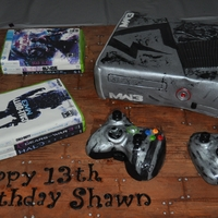 X-Box Cake! Created for a 13th Birthday, this young man love's his gaming! X-BOX, controllers, and games are all cake, covered in fondant, with...