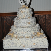 Gold And Silver Filigree Wedding Cake 4 tier Gold and Silver filigree covered Wedding Cake, adorned with gold and silver star flowers, blossoms, and orchids. Hand designed base...