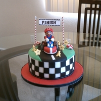 Mario Kart Cake For a Mario Kart themed birthday. Mario is made out of rice krispie treat and covered with fondant. Other characters are gumpaste.