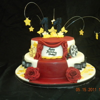 Hollywood Hollywood themed birthday cake covered with fondant. Roses, stars, film, reel, and tickets made with gumpaste and hand painted.