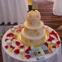 Gold And Ivory 3tier winter wedding cake. 2 tiers were dummies. The cake was covered in ivory fondant and then decorated with swirls and hand painted gold...