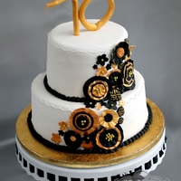 Black & Gold Ruffled Flower Cake This cake was made for a 70th surprise birthday party. It was made to match the black and gold colors and linens with gold flowers. Fondant...