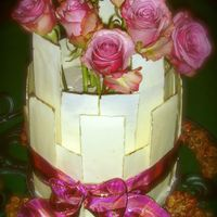 Romantic White Chocolate With Gold Detail & Roses Cake This two layer cake is surrounded by hand made white chocolate panels with hand painted gold edging. The cakes are covered in white...