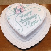 "1303328486.jpg 8"" heart cake iced with snow white buttercream icing. 5 royal icing rose flowers make 2 days ahead of time. Leaf tip leaves. #5 tip..."
