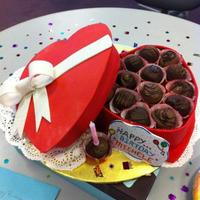 "Seasonal Cakes  Red velvet cake covered in fondant made to look like box of chocolate truffles. The ""lid"" and box are the cakes and the ""..."