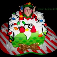 This Little Elf Has Gotten Himself All Tangled Up Cake Present Figure Lights Tissue Paper Made Of Gumpaste Amp Modeling Chocolate This little Elf has gotten himself all tangled up. Cake present. Figure, lights, tissue paper made of gumpaste & modeling chocolate