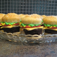 "Cheeseburger Cupcakes Vanilla cupcakes with brownie ""burger"", marshmallow fondant cheese, and buttercream ketchup, mustard and lettuce."