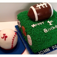 Sports Theme 1St Bday Buttercream grass covered cake. Fondant covered football and baseball.