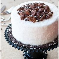 Cranberry, Coconut And Candied Nut Cake This is a cranberry- coconut cake, filled with buttercream and crushed candied nuts. it's covered in more buttercream and shredded...