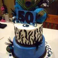 50Th Peacock Birthday Covered in butter cream, mmf details, plastic metallic rings, and handmade wooden topper.