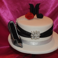 Black & White Glamor Black and white cake with fondant initial and rose. Non edible ribbon and shoe is a ring holder.
