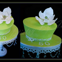 Lime Green Freshness!  This is a pretty lime green and white, one tier topsy turvy. A gorgeous sugar Southern Magnolia sits atop. Cake is a milk chocolate mud,...