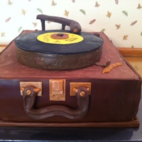 50S Music Theme Birthday. Suitcase Record Player With Record Albums. 60th surprise birthday party. chocolate ganache top, chocolate LMF sides, modeling chocolate accents.