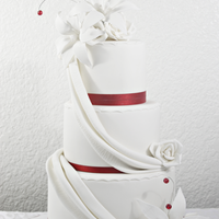 Red & White Wedding Cake W/ Drapes And Lilies  Red velvet cake (8,6 & 4 inches)...customer requested white and red only with lilies and roses. The ribbon and beads in the photo look...