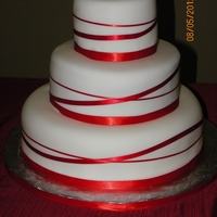 Red Ribbon Wedding Cake Bottom Tier: Strawberry cake/Cream Cheese frostingMiddle Tier: Chocolate Cake/ Peanut Butter Heaven filling/ GanacheTop Tier: Vanilla Cake/...