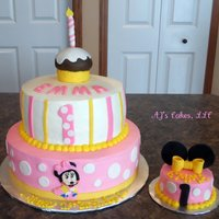 Pink Minnie Mouse Cake Cake is iced in buttercream with fondant accents. Minnie Mouse is handcut with fondant and cupcake is rice krispy treats with buttercream...
