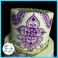 Hand Painted Henna Inspired Wedding Cake This cake is covered in ivory satin ice fondant, then hand painted with wilton gel color, last we added gold dragees and gold rope borders...