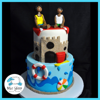 Beach Party Birthday Cake This fondant cake features a life preserver, beach ball, sandcastle (crusted with sugar) and two fondant figures of the birthday boys.