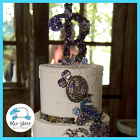 Vintage Wedding Cake This cake features an antique book cake as the base with a two tiered wedding cake set on top. The cake is fondant with fondant lace...