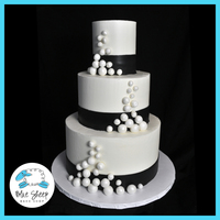 Black And White Buttercream Wedding Cake With Pearls This buttercream wedding cake features black fondant sashes and pearls.